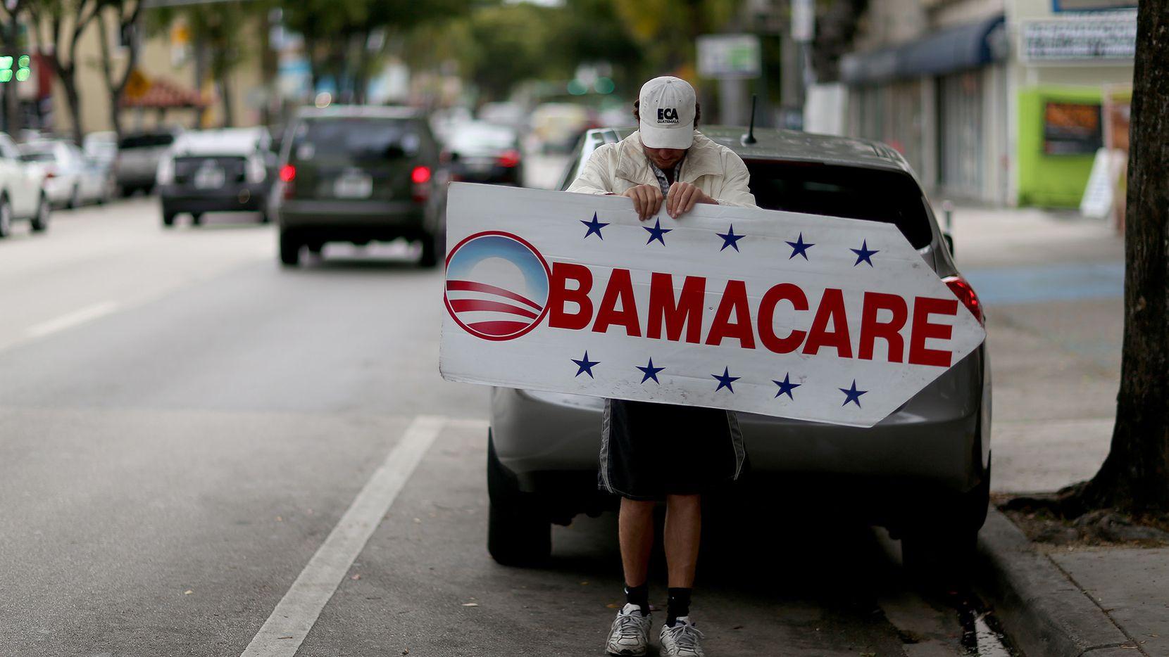 """Una persona promociona registros para el seguro médico conocido como """"Obamacare"""" en Miami, en 2015."""