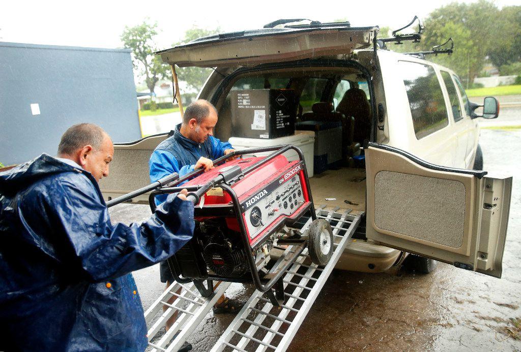 Repairman Ruben Rosas (left) of Daniel's Small Engine Repair helps John Valdivia load up his repaired generator.