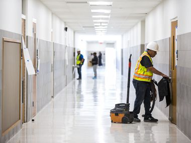 A worker moves cleaning equipment in a hallway on Thursday, December 19, 2019 at South Oak Cliff High School in Dallas, as part of a $52 million renovation to the campus. Dallas ISD is hoping voters approve a record-setting $3.7 billion bond package next month, allowing for similar work across the district's 226 campuses.