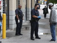 Practicing social distancing amid COVID-19 concerns, police officers speak with a man in downtown Dallas, Friday, April 3, 2020.