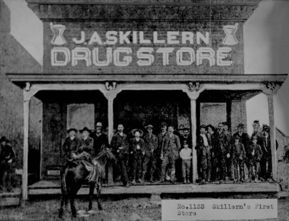 Photograph of J.A. Skillern and a crowd of men in front of the first Skillern's Drug Store in Lewisville, circa 1885.