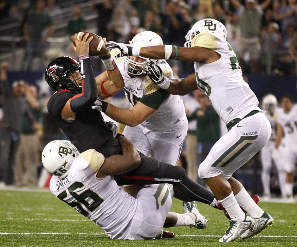 Baylor Bears defensive end K.J. Smith (56), linebacker Aiavion Edwards (20) and defensive tackle Byron Bonds (96) combined for the sack of Texas Tech Red Raiders quarterback Patrick Mahomes (5) on a late fourth quarter two-point conversion that would have tied the game at AT&T Stadium in Arlington, Texas, Saturday, November 29, 2014. Baylor went on to win 48-46. (Tom Fox/The Dallas Morning News)