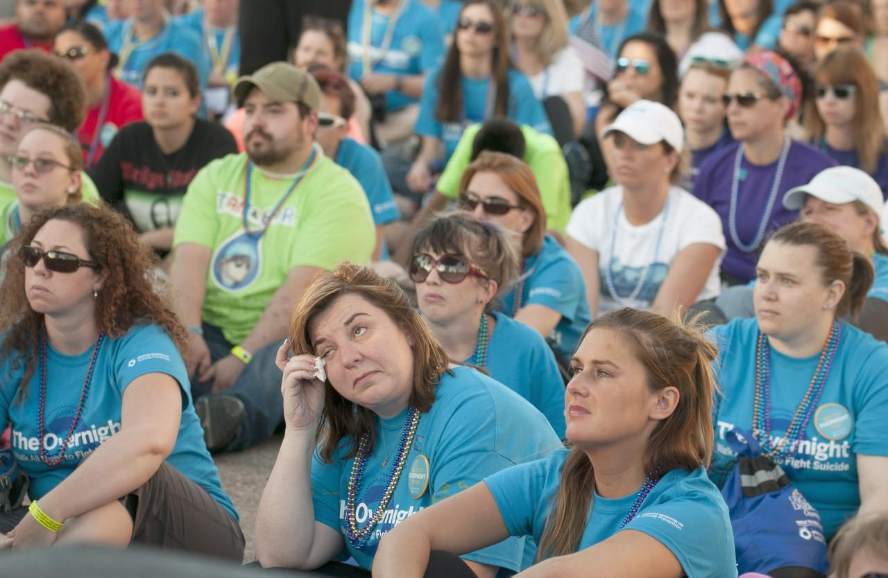 Erin Kelley wiped away a tear Saturday at Dallas City Hall as a crowd listened to speakers tell about family members lost to suicide. The event launched an overnight walk to call attention to suicide and raise money to fight it.