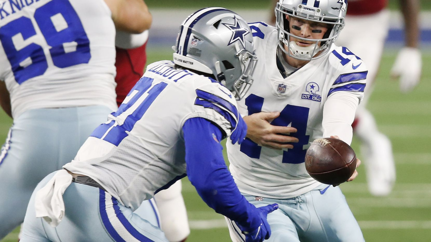 Cowboys quarterback Andy Dalton (14) hands the ball off to running back Ezekiel Elliott (21) during a game against the Cardinals at AT&T Stadium on Monday, Oct. 19, 2020, in Arlington.