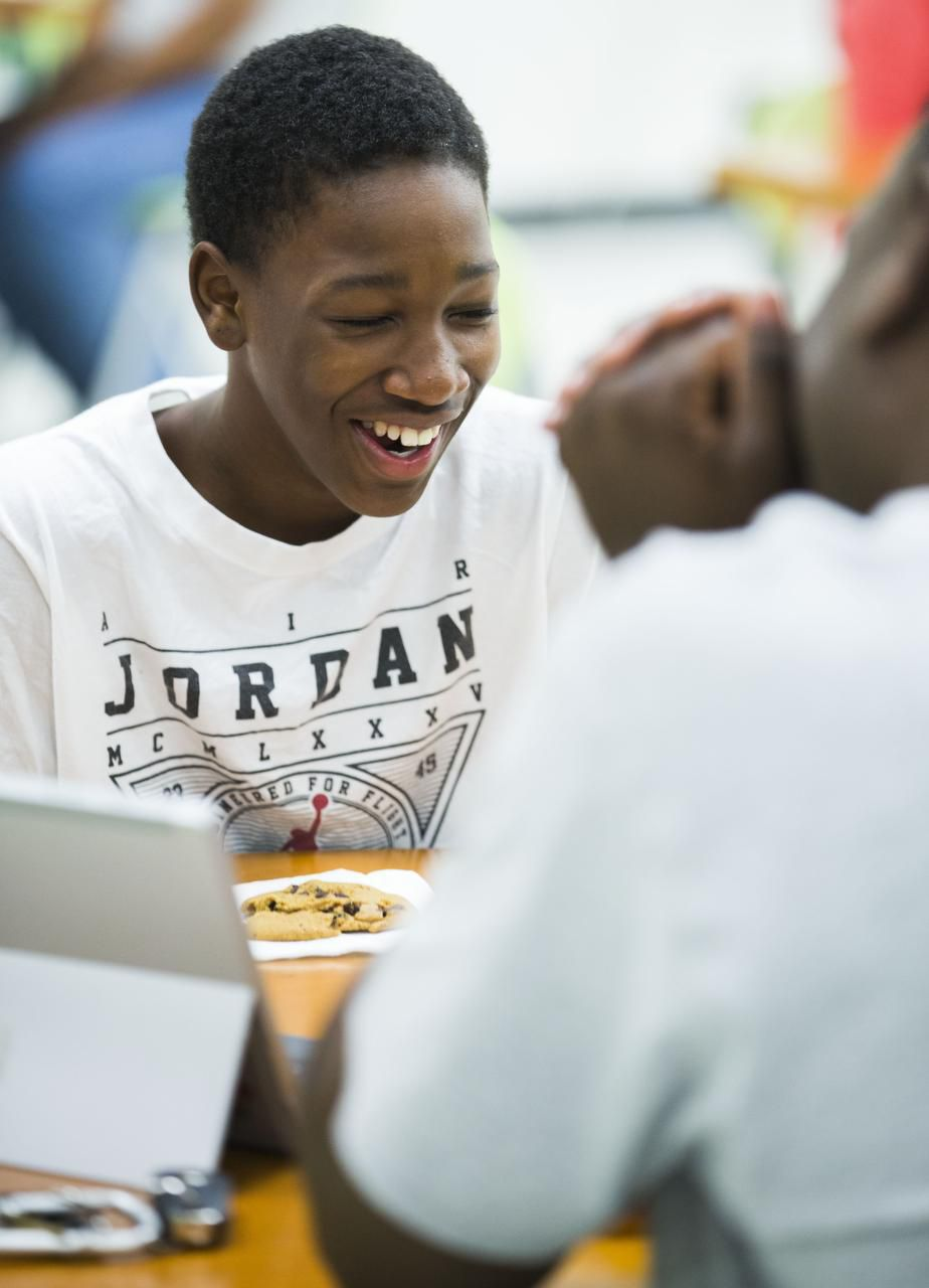 Jody Legans Jr., 14, laughs with his father, Jody Legans, during a community barecue for Innovation, Design and Entrepreneurship Academy at Fannin High School in Dallas.