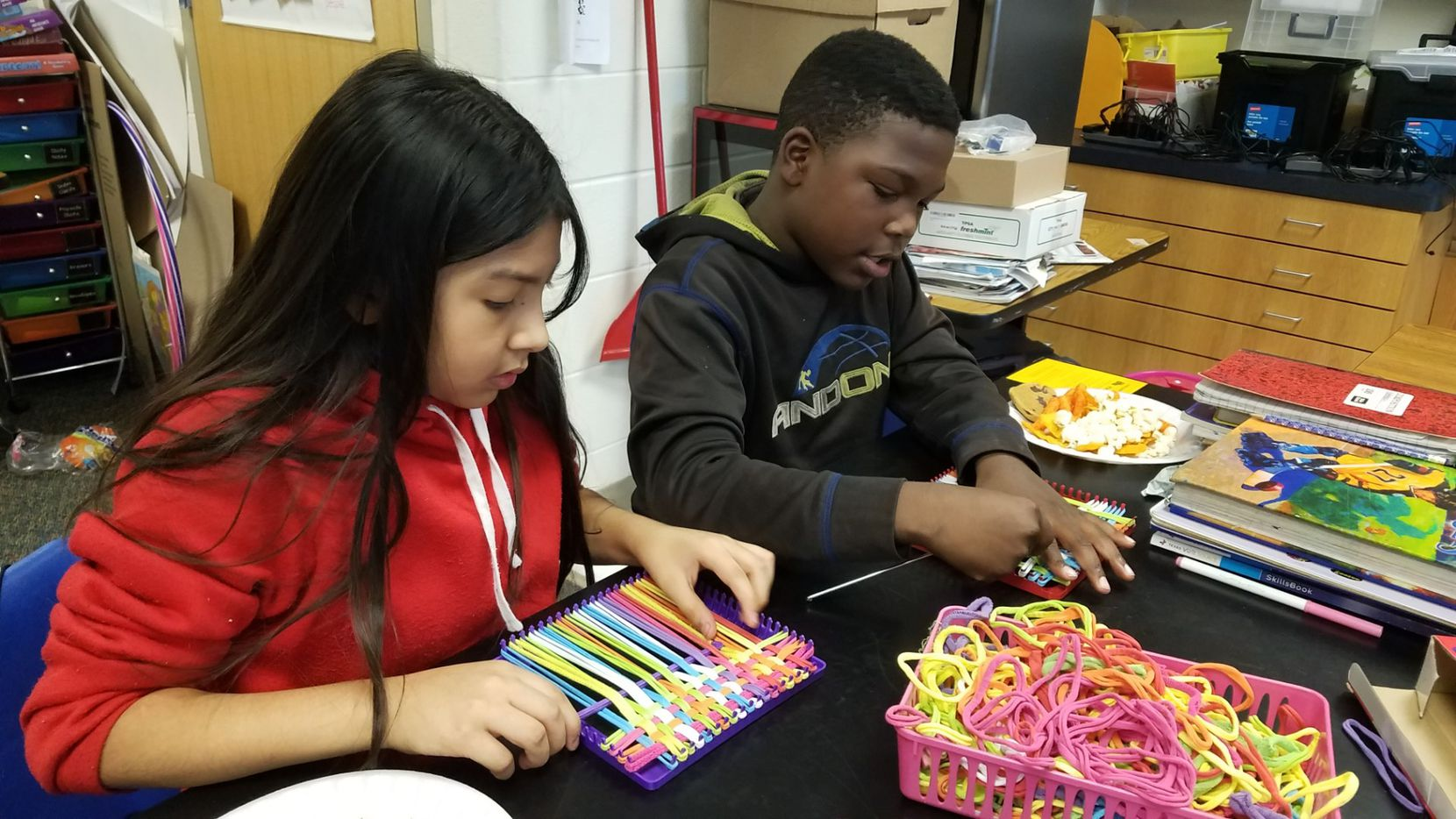 Diana Ramirez, left, and Robert Reddick work on their crocheting at Wilmer-Hutchins Elementary School. The group of fifth-graders spend a portion of their recess learning how to crochet. Their teacher, Charlotte Geisler, collects their creations and donates them to local homeless shelters.