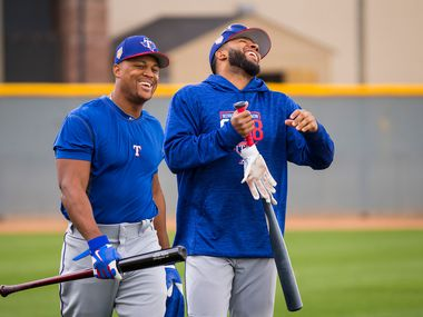 Texas Rangers third baseman Adrian Beltre (left) and shortstop Elvis Andrus laugh as they take the field for a spring training workout at the team's training facility on Monday, Feb. 19, 2018, in Surprise, Ariz.