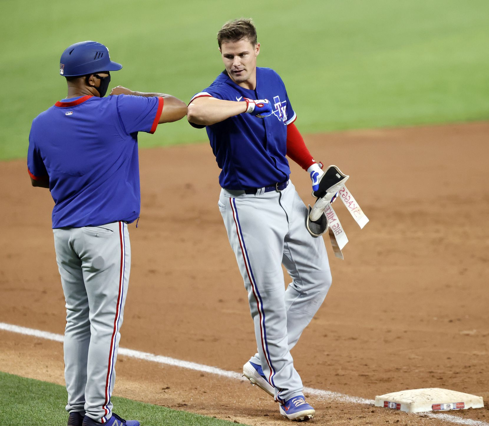 Texas Rangers outfielder Scott Heineman receives an elbow bump from third base coach Tony Beasley after his triple during a simulated Summer Camp game at Globe Life Field in Arlington, Texas, Thursday, July 9, 2020. (Tom Fox/The Dallas Morning News)
