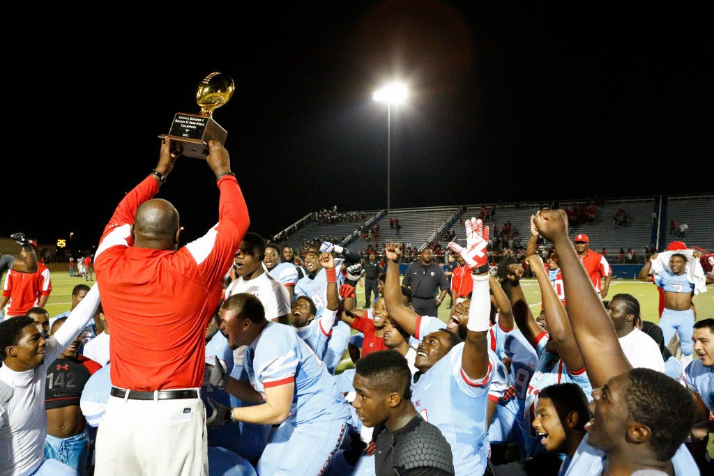 Skyline's head coach, Reginald Samples, holds the trophy up after beating Spring Westfield, 38-33, in the Class 5A Division I Region II semi-finals at the Georgetown ISD Athletic Complex in Georgetown, Texas, on December 1, 2012.  (Stan Olszewski/The Dallas Morning News)