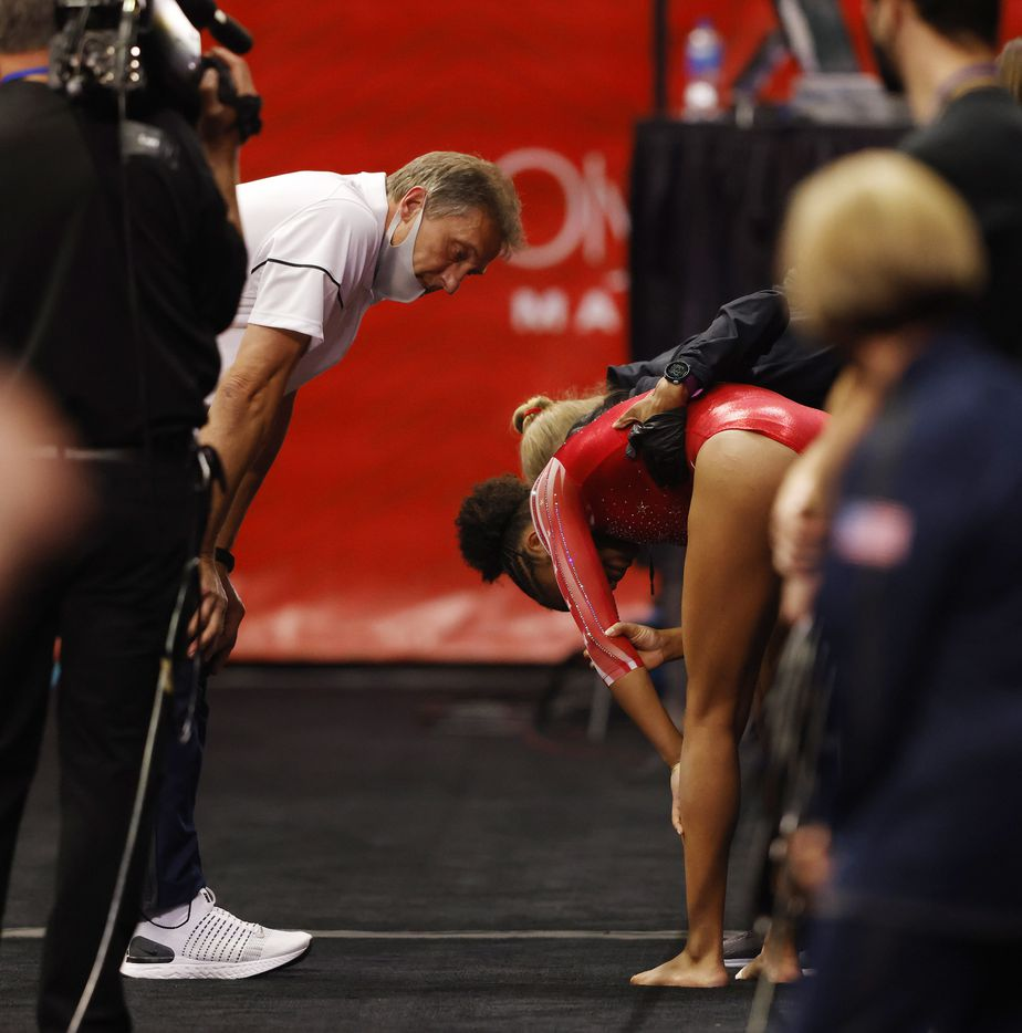Skye Blakely of WOGA is tended to at the vault station by coach Evgeny Marchenko and medical staff after injuring herself during warmups prior to competing in day 1 of the women's 2021 U.S. Olympic Trials at America's Center on Friday, June 25, 2021 in St Louis, Missouri.(Vernon Bryant/The Dallas Morning News)
