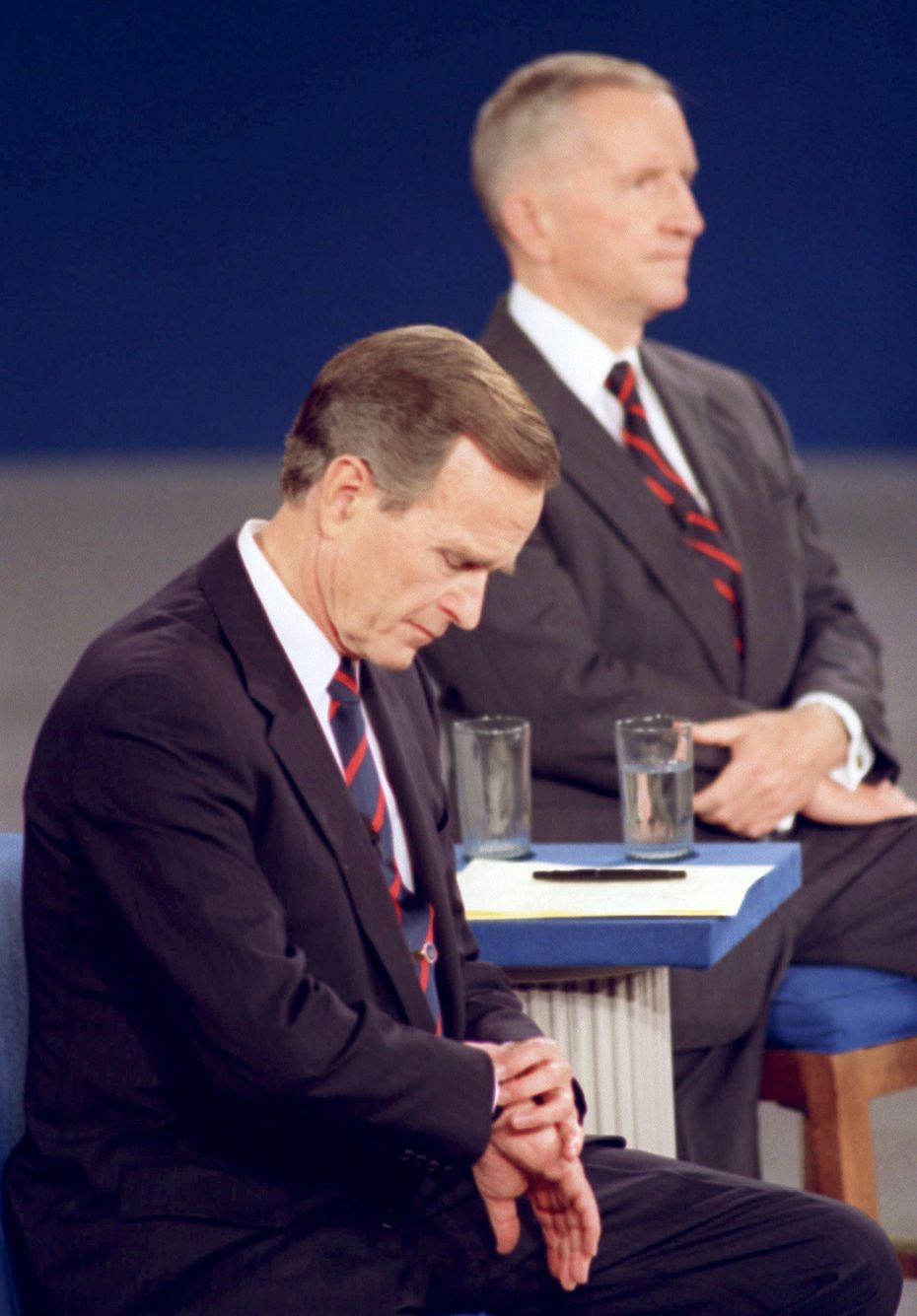 In a classic debate moment, President George H.W. Bush looks at his watch during a presidential debate at the University of Richmond in October 1992. Independent candidate Ross Perot is at right. Bush later lost the election to Bill Clinton.