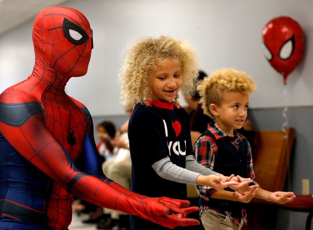 Chase Blackmore, dressed as Spiderman, poses for photos with adopted siblings Brett Sims (middle), 5, and Bolton Sims, 4, during National Adoption Day at Henry Wade Juvenile Justice Center in Dallas on Saturday, Nov. 18, 2017.