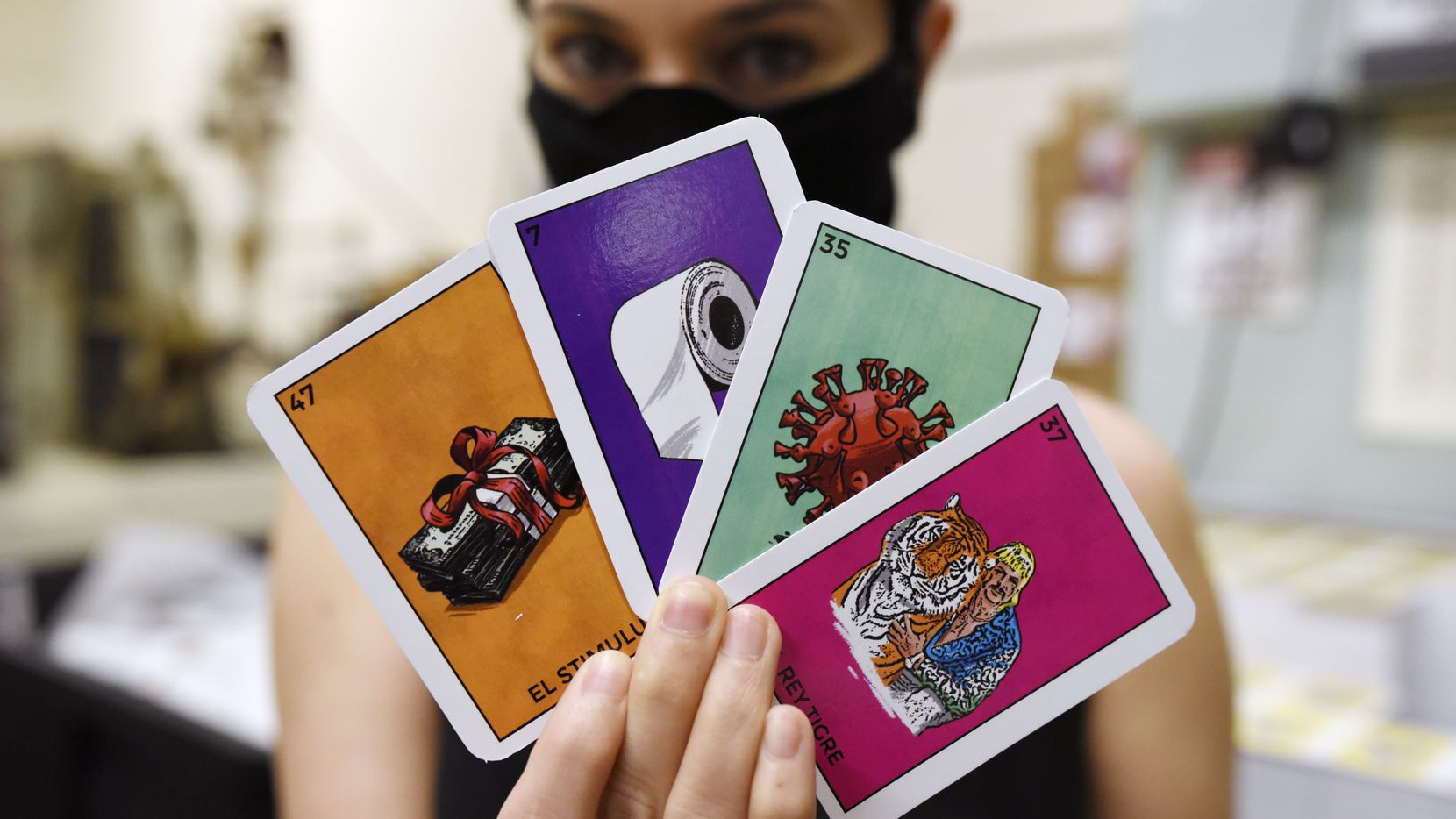 Alyssa Peña, director of business development for Versa Printing Inc. in Dallas, shows a few of the cards the company is producing for its coronavirus-themed lotería board game.