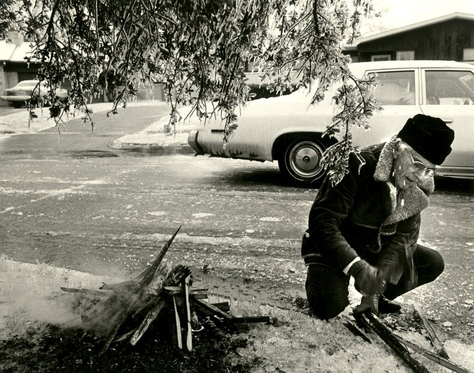 John Durmon tries to build a fire under a tree across the street from his home at 6527 Axton to save the tree from ice.