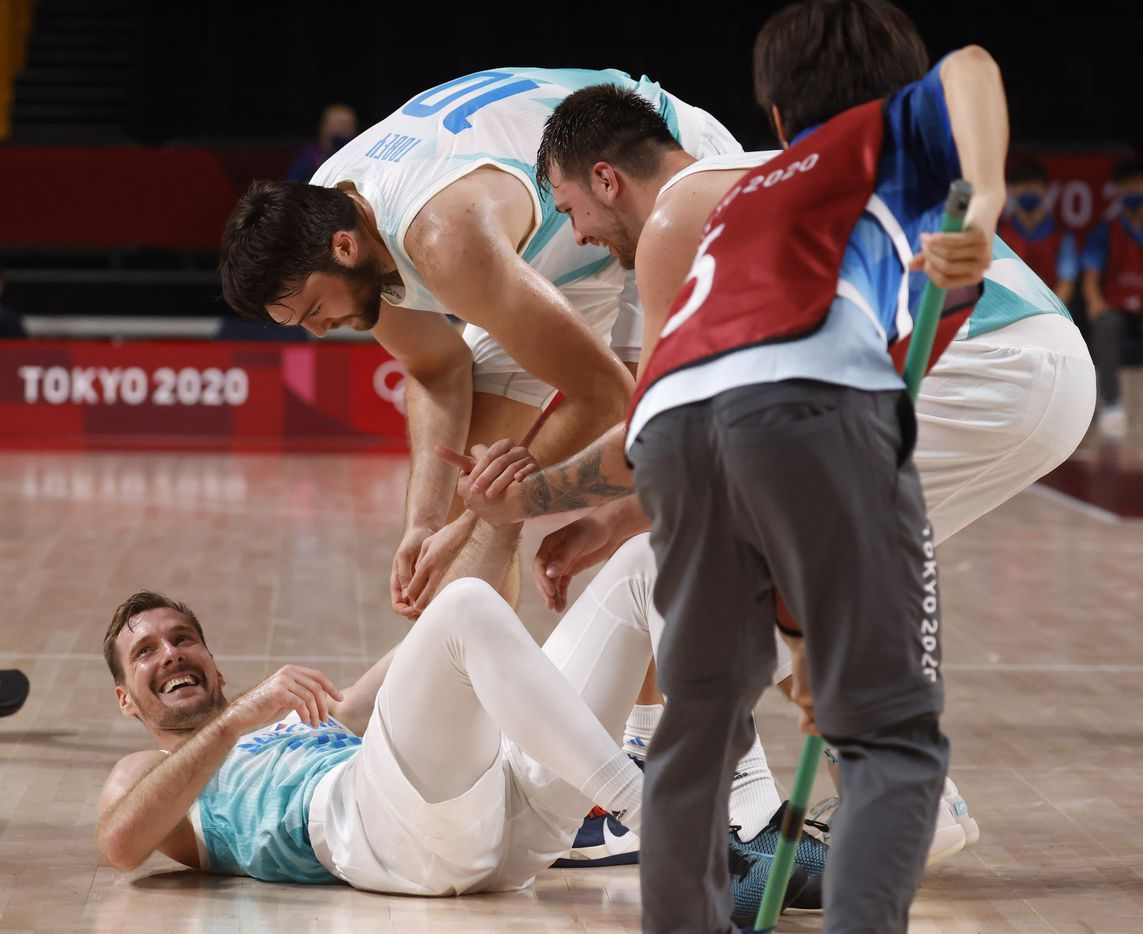 Slovenia's Zoran Dragic (30) laughs as Mike Tobey (10) and Luka Doncic (77) help him up after he dove after a loose ball in play against Germany during the second half of play of a quarter final basketball game at the postponed 2020 Tokyo Olympics at Saitama Super Arena, on Tuesday, August 3, 2021, in Saitama, Japan. (Vernon Bryant/The Dallas Morning News)