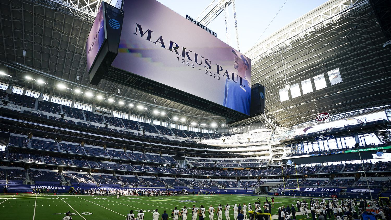 Dallas Cowboys players stand for a moment of silence honoring strength and conditioning coach Markus Paul, who died Wednesday evening after having a medical emergency during Tuesday's practice, before an NFL football game against the Washington Football Team at AT&T Stadium on Thursday, Nov. 26, 2020, in Arlington.