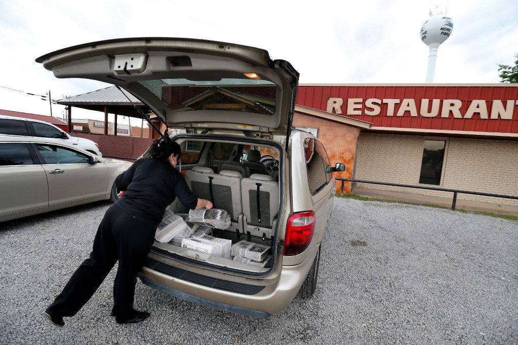 The Normangee Star newspaper owner and editor Sylvia Moss grabs another bundle of papers from her delivery van as she makes a stop in downtown Normangee, Texas, Tuesday, May 23, 2017.
