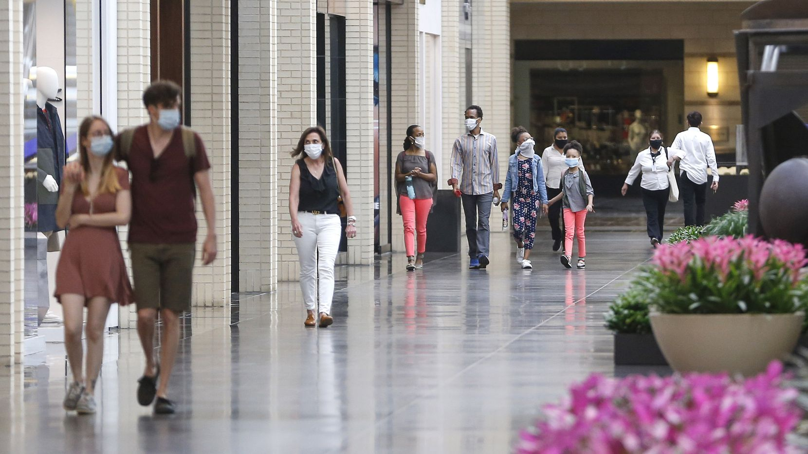 Shoppers walk through NorthPark Center mall on May 1, 2020 in Dallas. Gov. Greg Abbott's executive order requiring Texans to stay at home expired on April 30, which allowed businesses to reopen under restricted conditions.