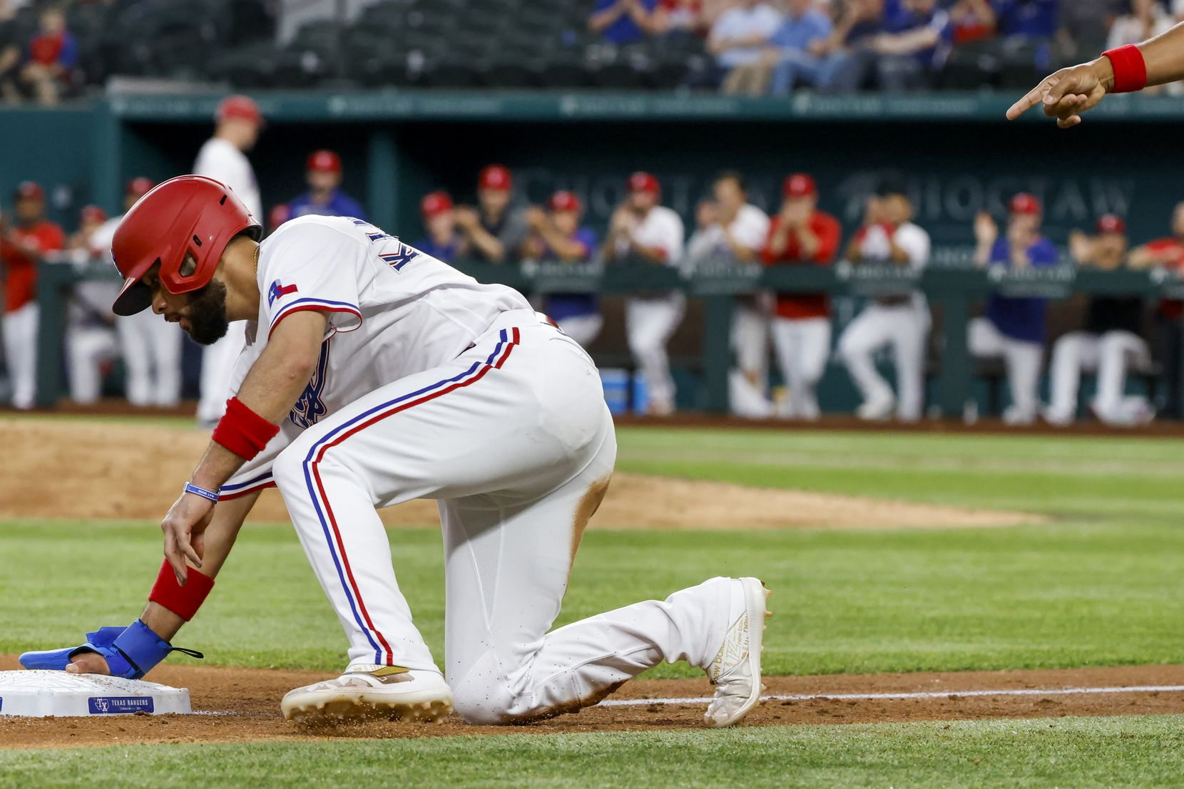 The Rangers' Isiah Kiner-Falefa arrives on third base at Globe Life Field after Brock Hold lined out to center against the San Francisco Giants on June 9.