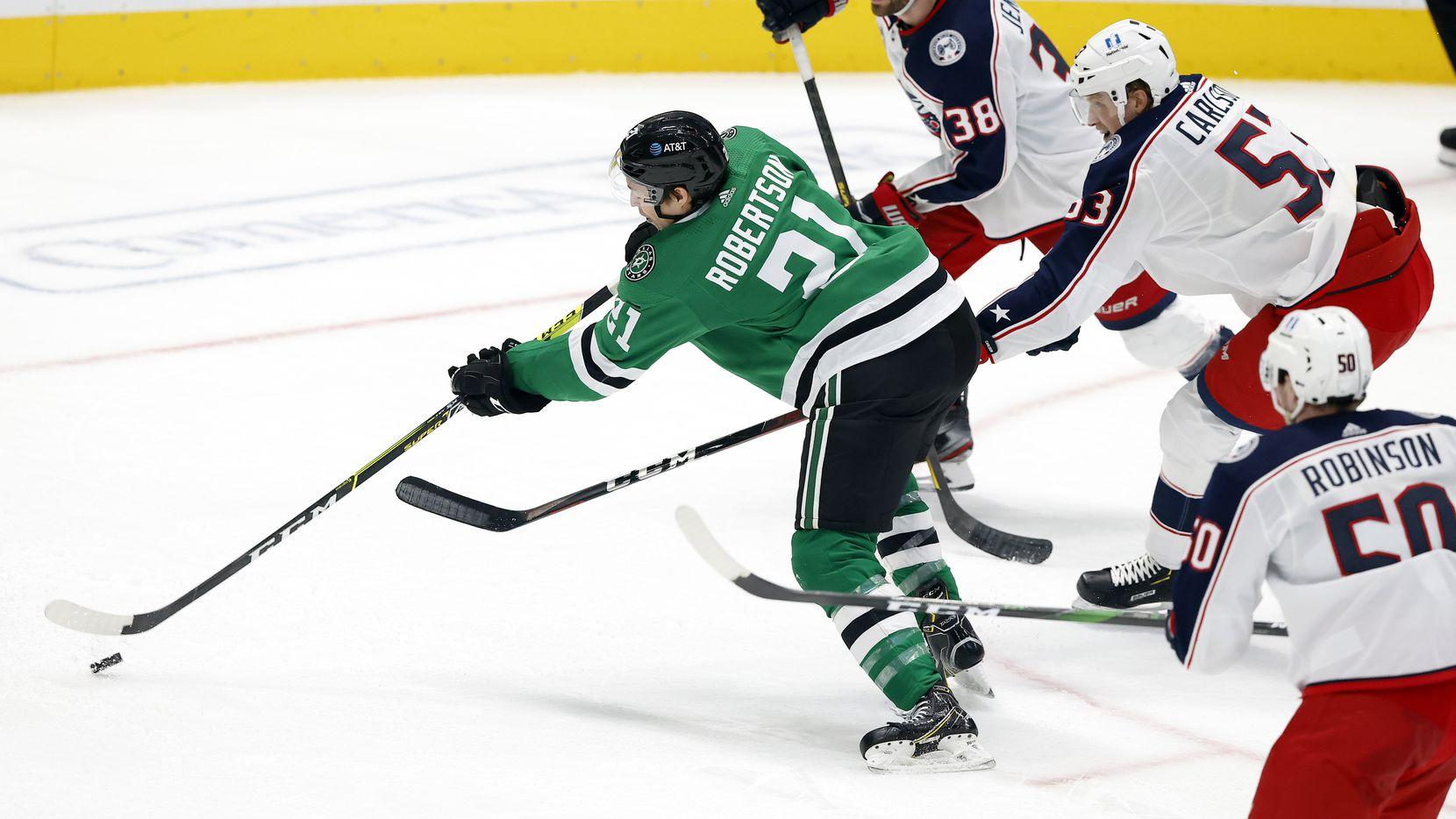 Dallas Stars left wing Jason Robertson (21) shoots and scores a third period goal against Columbus Blue Jackets defenseman Gabriel Carlsson (53) and center Boone Jenner (38) at the American Airlines Center in Dallas, Thursday, March 4, 2021. The Stars fell to the Blue Jackets, 3-2. (Tom Fox/The Dallas Morning News)