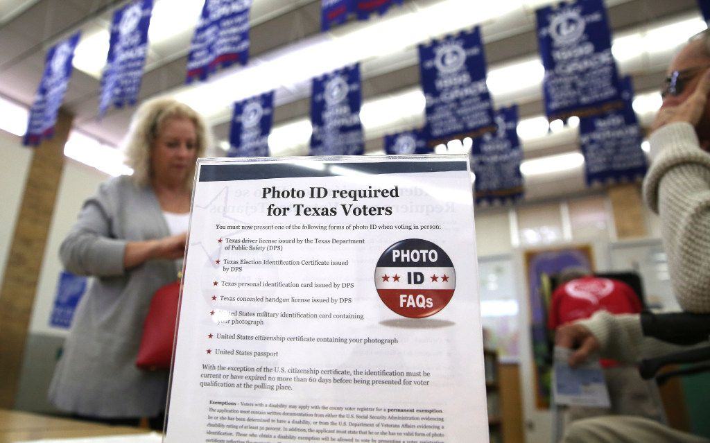 In this March 1, 2016, file photo, a sign tells voters of voter ID requirements before participating in the primary election at Sherrod Elementary school in Arlington, Texas.  (LM Otero/The Associated Press)