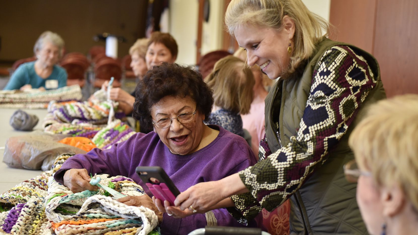 Volunteers Annie Palacios (left) and Brianna Brown look at a photo on Brown's cellphone as the women take a brief break from crocheting plastic bags into floor mats.
