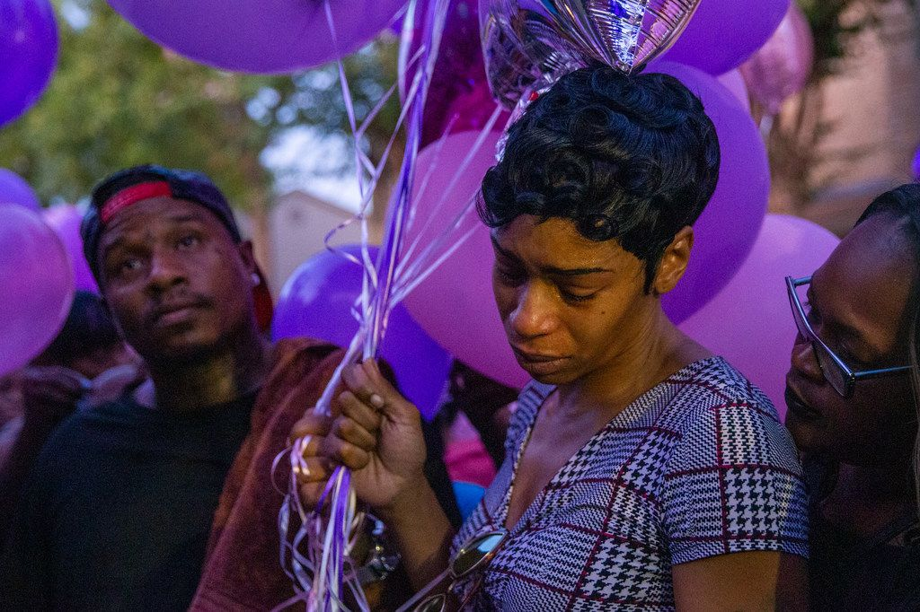 Sontravia Elder (center) and her immediate family attend a vigil honoring the life of her 9-year-old daughter, Brandoniya Bennett, at the Roseland Townhomes on Friday, Aug. 16, 2019.