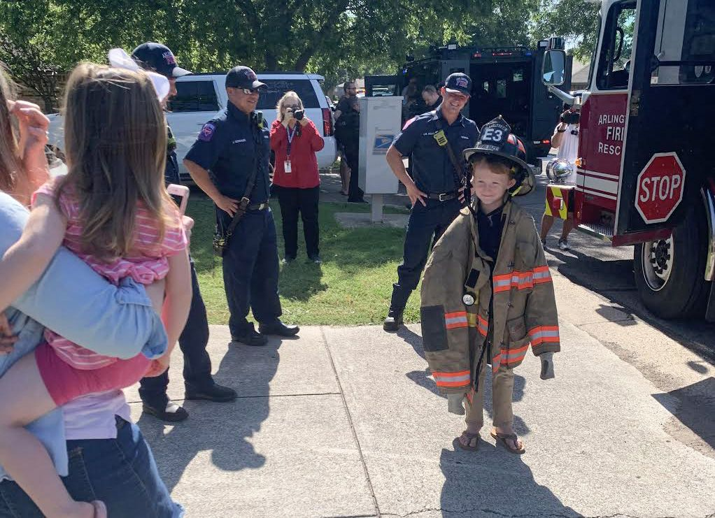 Carter Woodruff, 7, tries on an Arlington Fire uniform on Tuesday, May 19, 2020, in Arlington, Texas. The department and Arlington Police honored him for helping save his sister's life.