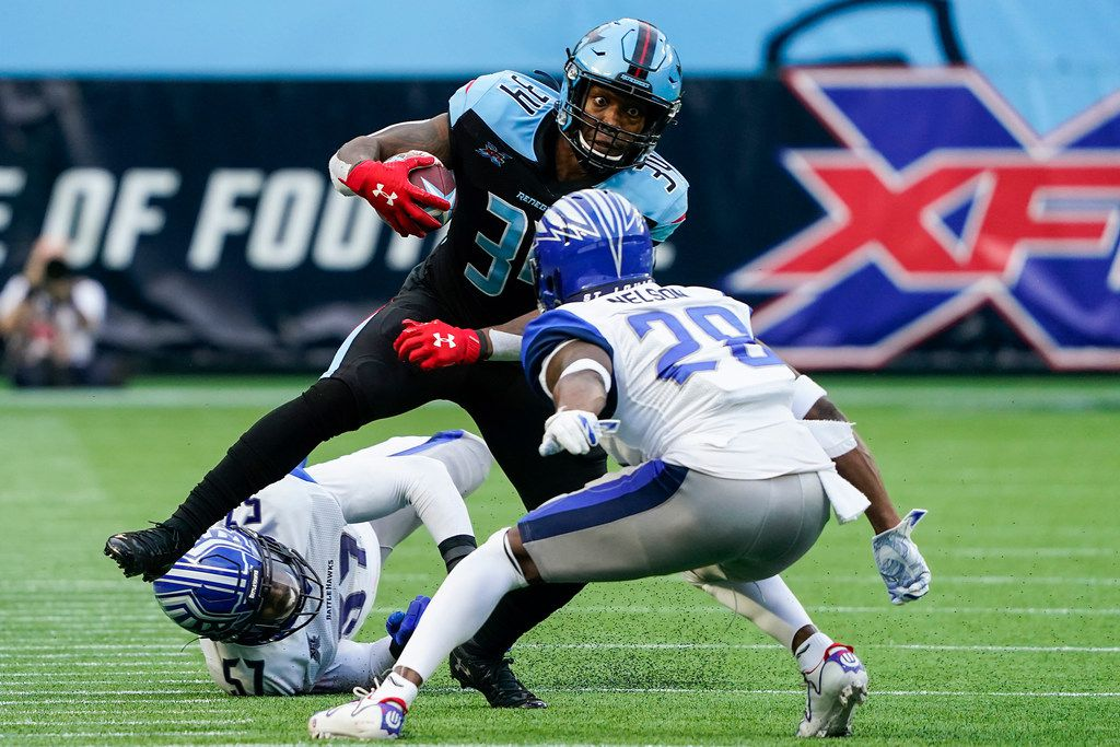 FILE - Dallas Renegades running back Cameron Artis-Payne (34) is brought down by St. Louis Battlehawks linebacker Terence Garvin (57) and cornerback Robert Nelson (28) during the first half of an XFL game at Globe Life Park on Sunday, Feb. 9, 2020, in Arlington.