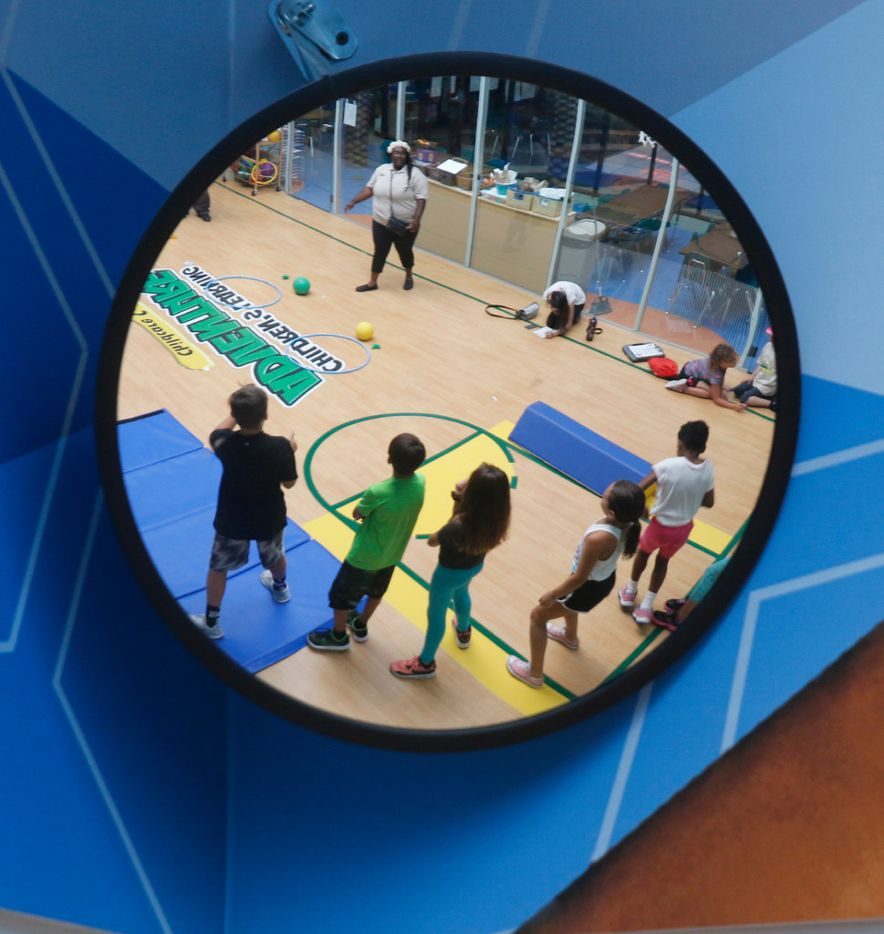 Children are reflected in a mirror as they prepare to run a small obstacle course in the gym at at the Children's Learning Adventure Childcare Centers in McKinney on June 14.
