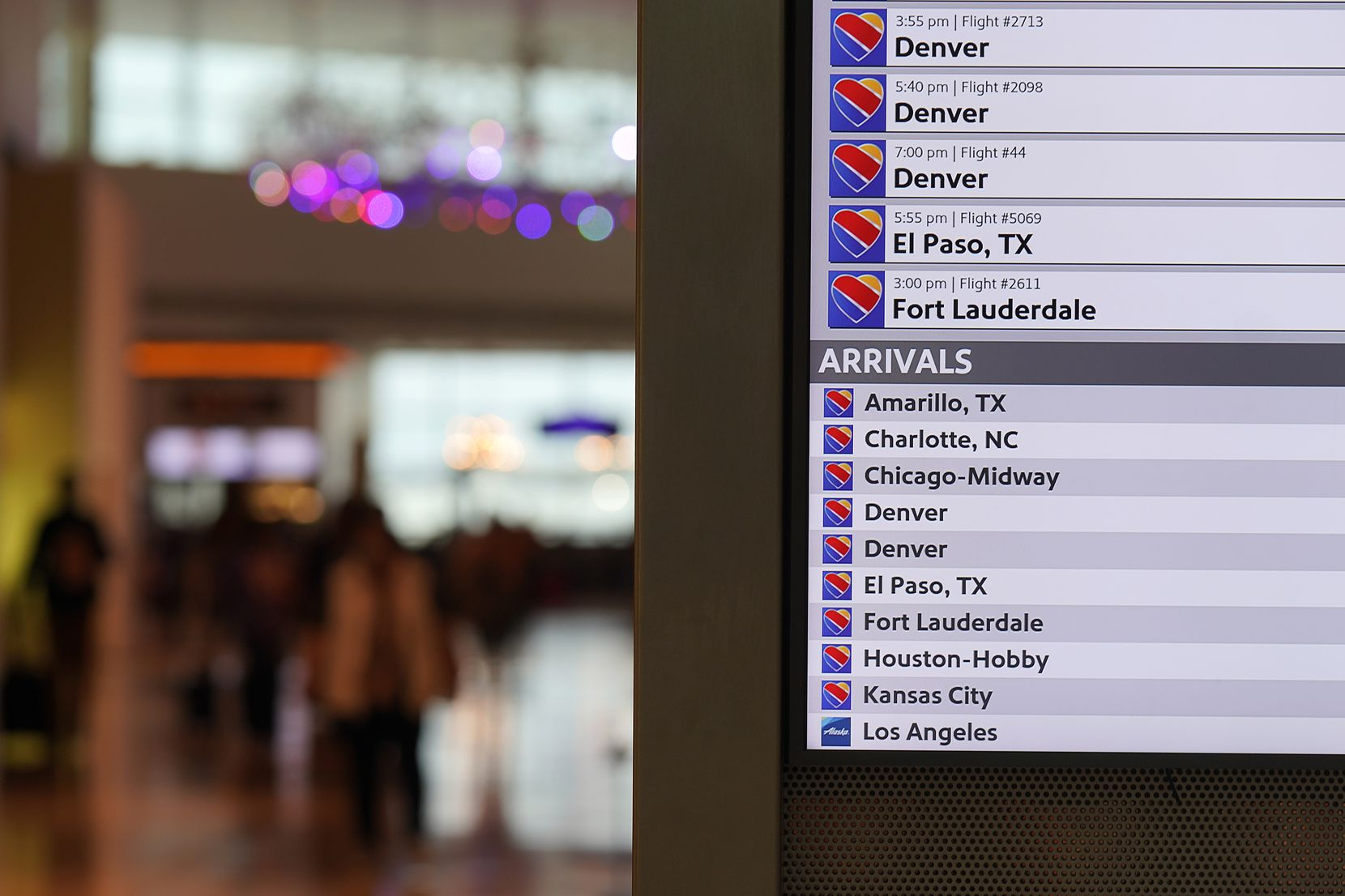 A flight status display show Southwest Airlines arrivals and departures at Dallas Love Field on Jan. 7.