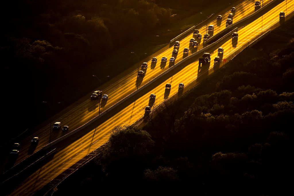 Traffic travels on C.F. Hawn Freeway passing through the Great Trinity Forest as the sun sets.