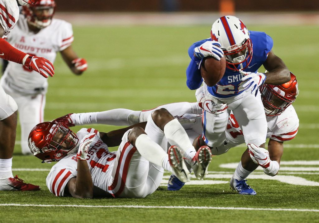 Southern Methodist Mustangs wide receiver Myron Gailliard (22) is brought down by Houston Cougars cornerback Joeal Williams (13) and defensive back Gleson Sprewell (21) during a matchup between the Southern Methodist Mustangs and the Houston Cougars on Saturday, Nov. 3, 2018 at Ford Stadium in Dallas. (Ryan Michalesko/The Dallas Morning News)