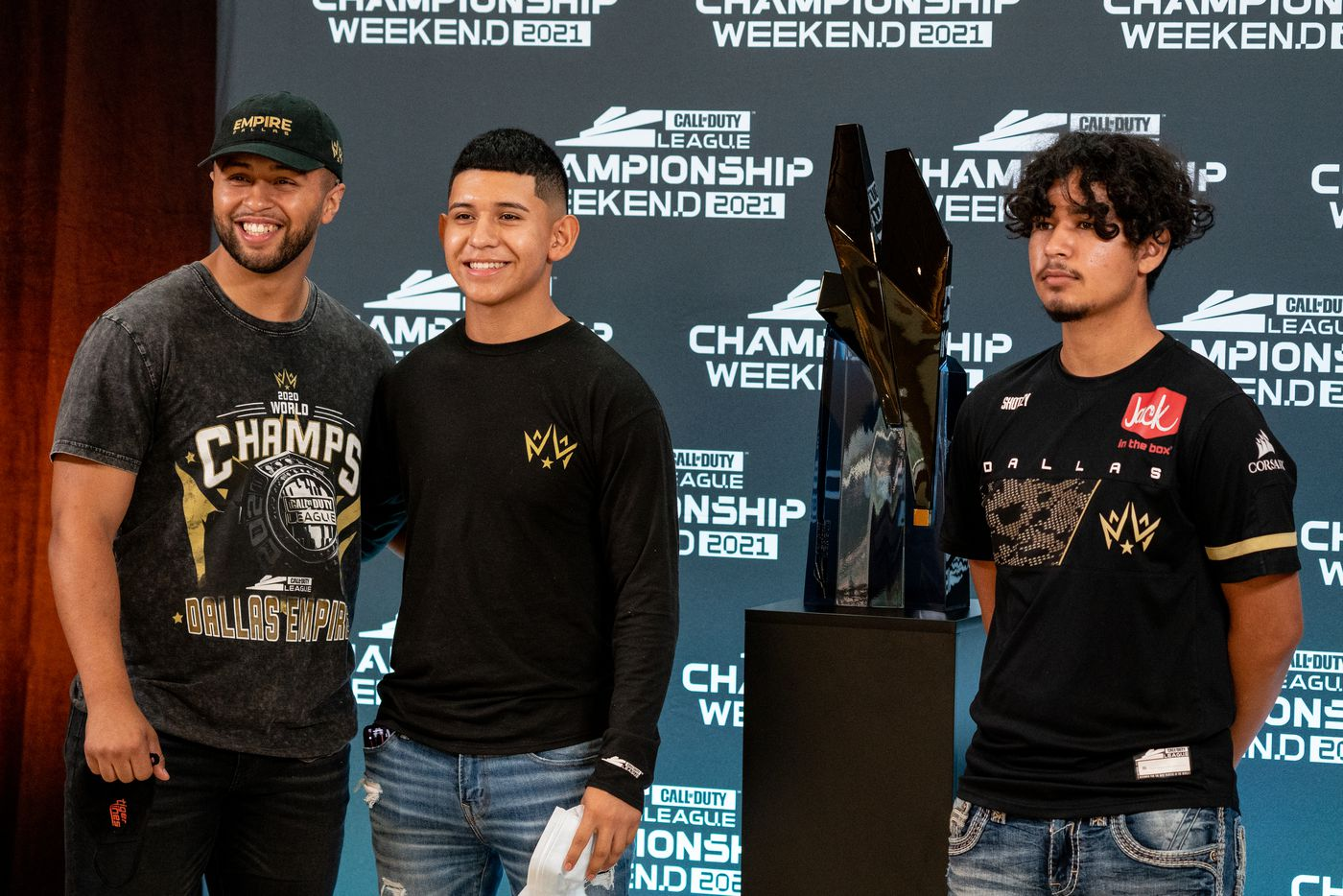 """From left, Steven Quevedo, Gabriel Castro, and Xavier Castro, brothers of Dallas Empire player Anthony """"Shotzzy"""" Cuevas-Castro, stand next to the Call of Duty league trophy before the start of the winners final between the Empire and the Atlanta FaZe at the Galen Center on Saturday, August 21, 2021 in Los Angeles, California.  (Justin L. Stewart/Special Contributor)"""