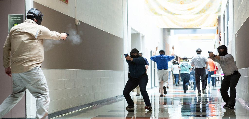 John Helenberg, (left) a Wilco reserve officer and instructor with the Texas Commission on Law Enforcement, plays the bad guy as he shoots at two school employees training to become school marshals during a practice drill at Windermere Elementary School in Pflugerville, Texas, on August 10, 2018.