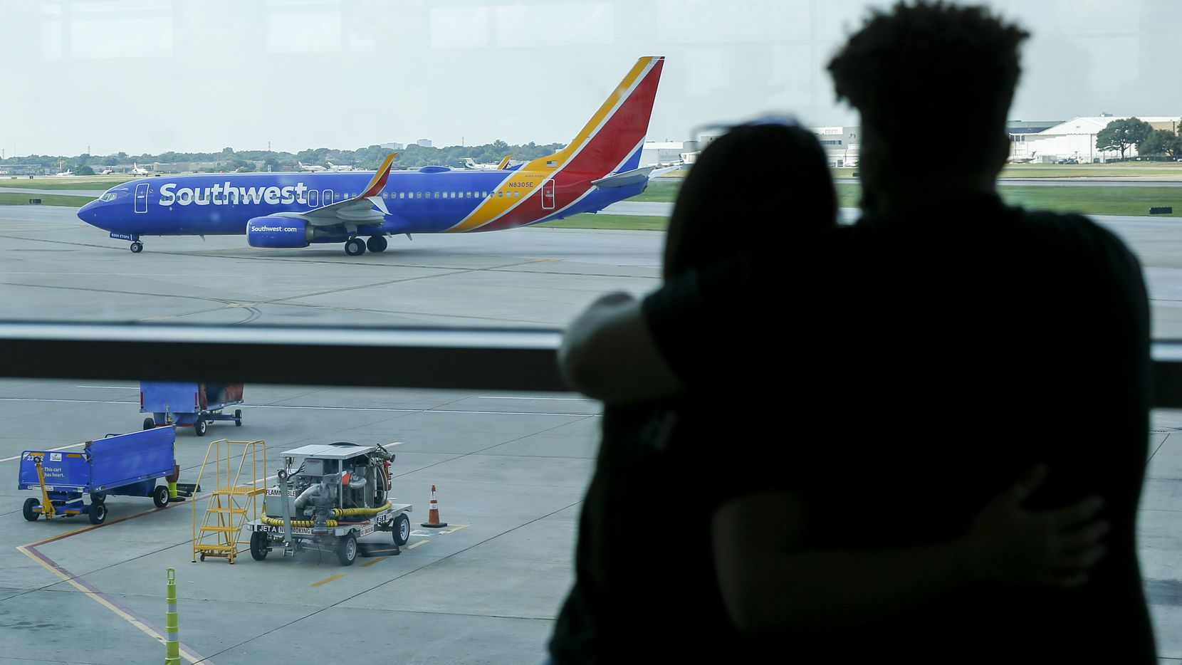 A couple watches as a Southwest Airlines flight taxis to the gate at Dallas Love Field.