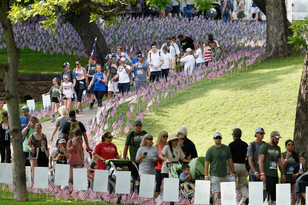 Participants walks pass flags and stories signs planted in the grass honoring police officers and firefighters planted along the route of Carry the Load fundraising walk on May 29, 2016 held at Reverchon Park in Dallas.