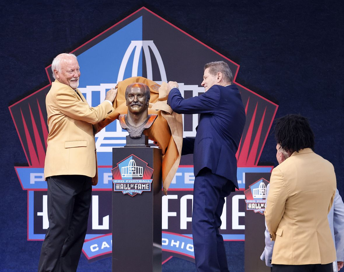 Pro Football Hall of Fame inductee Cliff Harris of the Dallas Cowboys (left) unveils his bronze bust with presenter and former Cowboy Charlie Waters during the Centennial Class of 2020 induction ceremony at Tom Benson Hall of Fame Stadium in Canton, Ohio, Saturday, August 7, 2021. (Tom Fox/The Dallas Morning News)