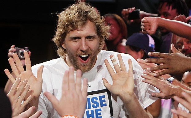 Fans high-five NBA Finals MVP Dirk Nowitzki as he makes his way to the stage during the Dallas Mavericks' championship celebration Thursday at American Airlines Center.