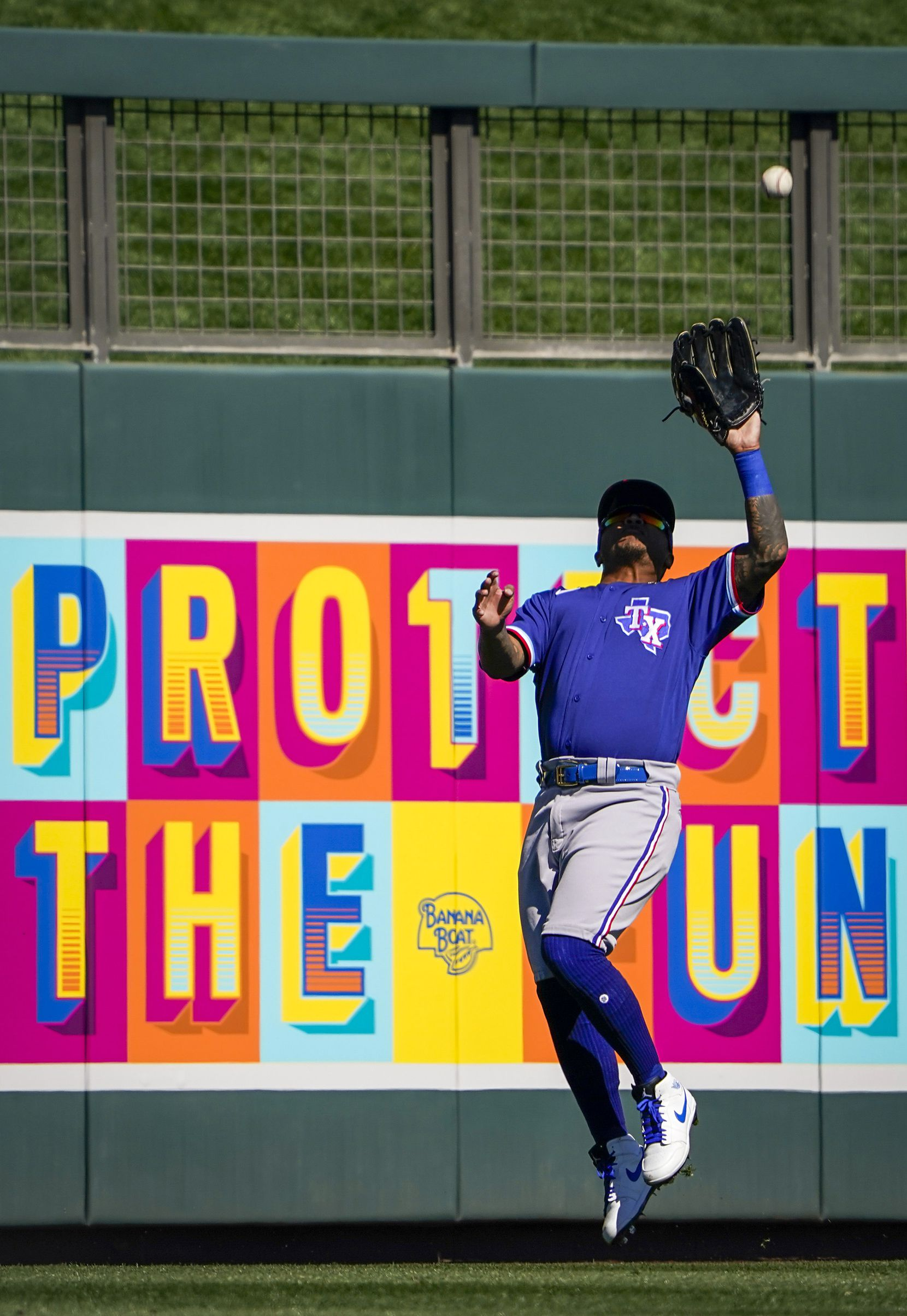 Texas Rangers outfielder Willie Calhoun makes a leaping catch on a line drive off the bat of Colorado Rockies shortstop Chris Owings during the third inning of a spring training game at Salt River Fields at Talking Stick on Wednesday, Feb. 26, 2020, in Scottsdale, Ariz.