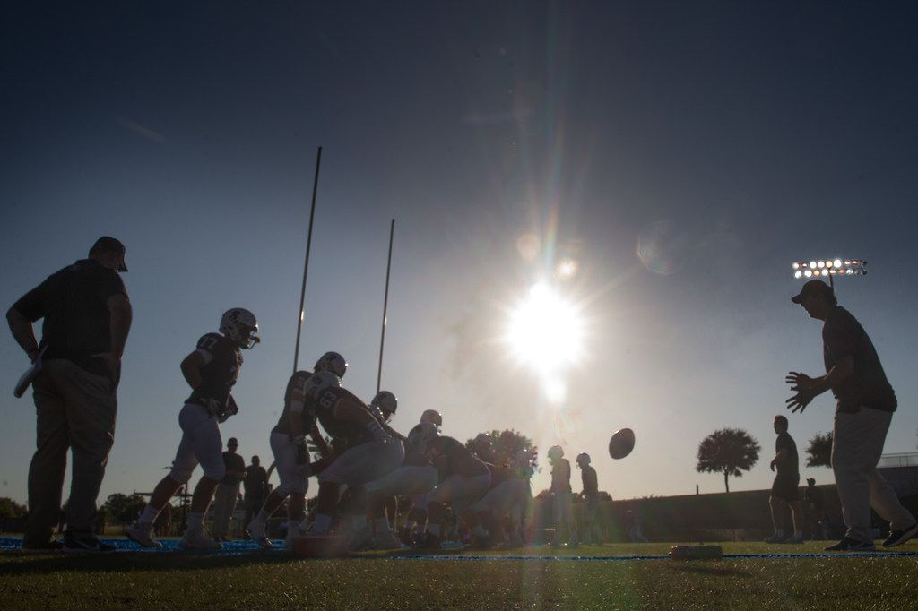 The sun begins to set behind the All Saints' Episcopal School varsity football team as they prepare for a game against Bishop Dunne Catholic School at Young Field McNair Stadium in Fort Worth, Texas, on Friday, Sep. 27, 2019. (Lynda M. Gonzalez/The Dallas Morning News)