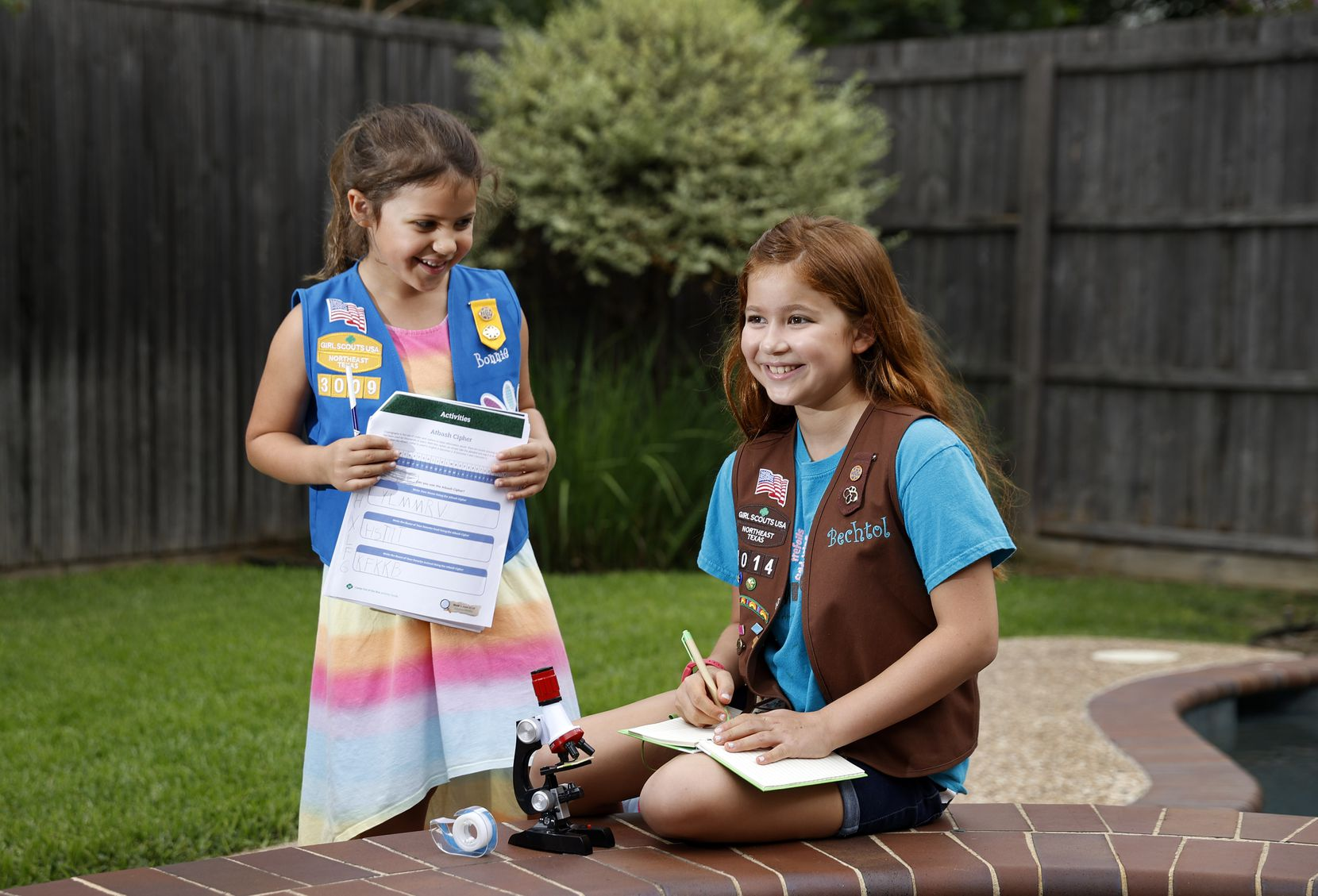 Daisy Scout Bonnie Garcia (left), 6, of Troop 3009 and her sister, Brownie Scout Bechtol Garcia, 9, of Troop 8014 pose for a photo in the backyard of their Dallas home. They are taking part in the Girl Scouts of Northeast Texas' Camp Out of the Box, which helps girls stay involved in their communities while learning STEM during the coronavirus pandemic. (Tom Fox/The Dallas Morning News)