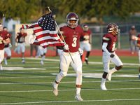 Heritage High School wide receiver Jordan Gregory (3) carries the United States flag as the team attempts to social distance as they take the field before kickoff as Heritage High School hosted Rock Hill High School at Memorial Stadium in Frisco on Thursday night, September 24, 2020.