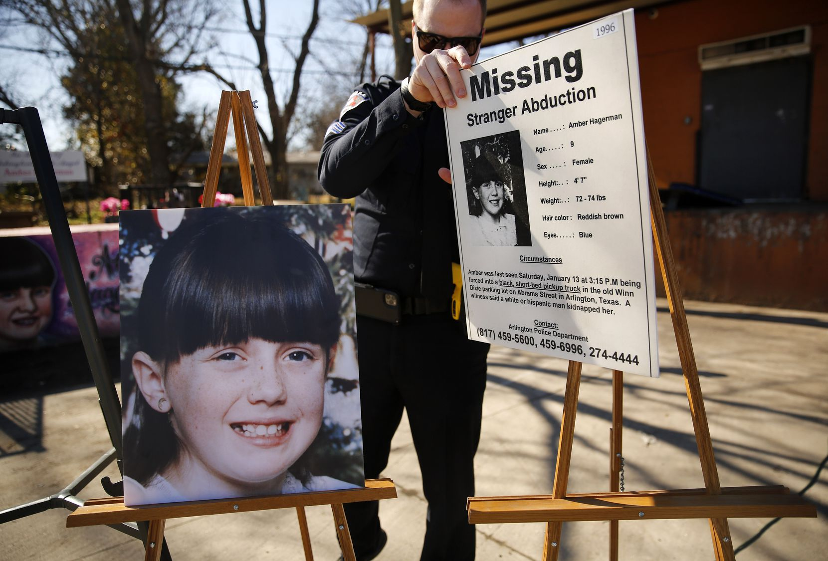 Arlington Police Sgt. Michael Chitty removes a the original 'Missing' alert and a photo of Amber Hagerman following a press conference at the abduction site on Abrams St. in E. Arlington, Texas, Wednesday, January 13, 2021.