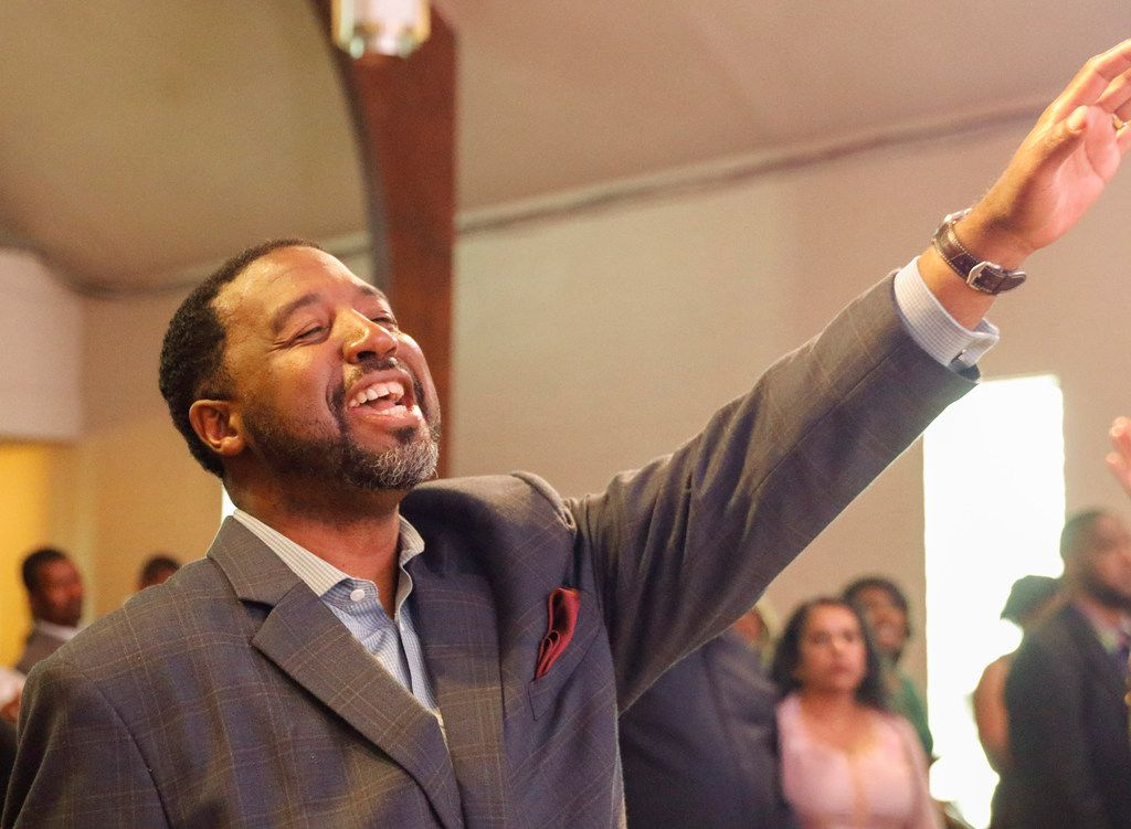 Pastor Andre Byrd Sr. of New Covenant Christian Fellowship Church raises his hand in praise during Sunday service. He will accompany the church's choir to Europe to perform in three cities in Spain later this month.