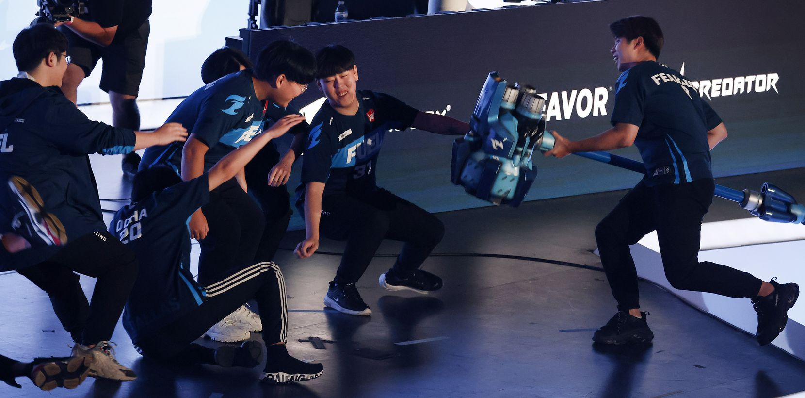 Dallas Fuel player Fearless (right) slams Reinhardt's hammer, knocking over his teammates during their Overwatch League introductions at Esports Stadium Arlington Friday, July 9, 2021. Dallas Fuel defeated the Houston Outlaws in The Battle for Texas, 3-0. It was the first in-person live competition for fans in over a year. Houston competed from their hometown. (Tom Fox/The Dallas Morning News)