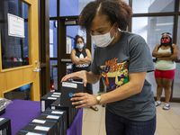 Parents wait as Principal Gabrelle Dickson grabs a WiFi hotspot provided by DISD for students at Young Women's STEAM Academy at Balch Springs on April 24, 2020 in Dallas. A district survey found that 30% of families responded that they didn't have internet at home.