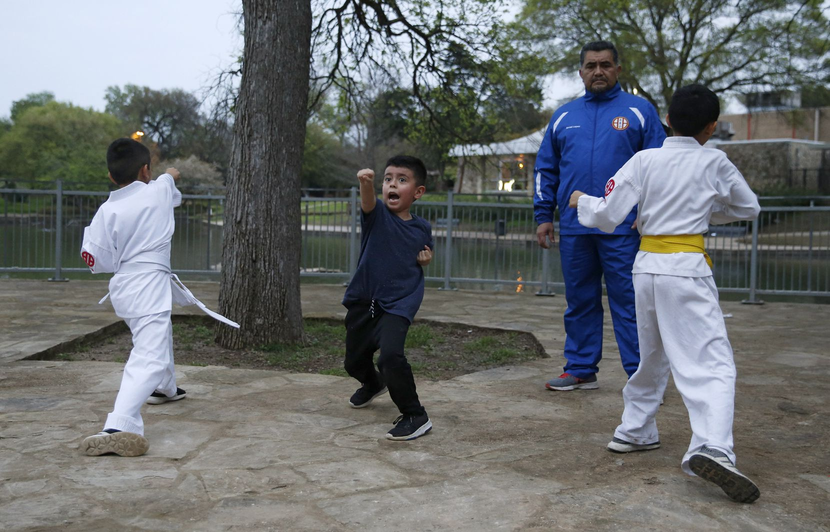 Leonardo Garcia, 6, practices his punches along with Gaviel Espinosa, 7, (left) and Alexander Valverde, 12, as Sensei Miguel Lopez of Shito Ryu Dallas watches during a no-contact karate class at Kidd Springs Park in Dallas.