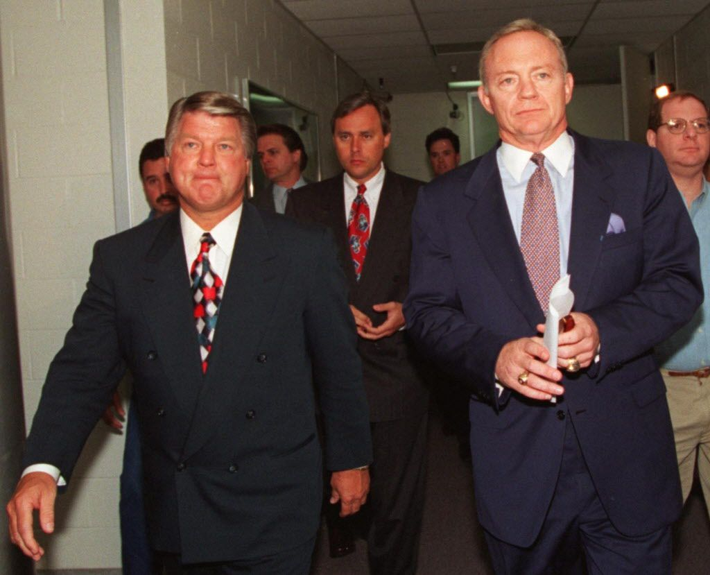 Jimmy Johnson (L), with a concerned look on his  face, walks past the Cowboy's locker room March 29, 1994, with Jerry Jones on their way to a news conference at Valley Ranch where Johnson announced that he would not coach the Dallas Cowboys anymore.