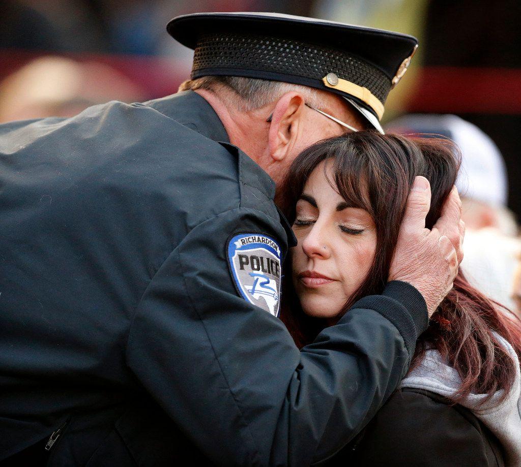Richardson police chief Jimmy Spivey hugs Nicole Sherrard, wife of slain Richardson police officer David Sherrard, after Spivey spoke during a vigil for Sherrard outside the Richardson Civic Center in Richardson, Texas, Sunday, February 11, 2018.